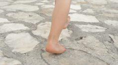 bare-feet-walking-over-stone-beach